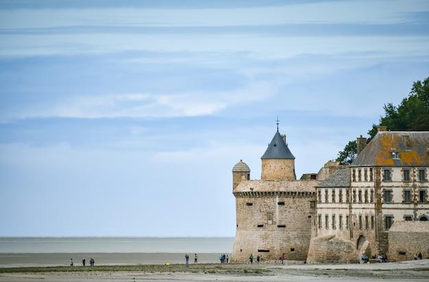 Turistas na praia e uma das torres da muralha do mont saint michel