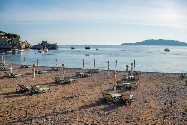 Turistas nadam no mar adriático durante o pôr do sol.