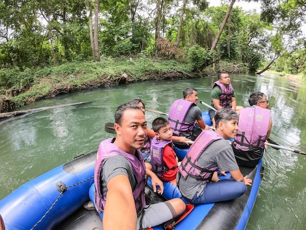 Turistas no barco inflável que flutuam na água no rio o fluxo da represa de kaeng krachan em phetchaburi em tailândia.