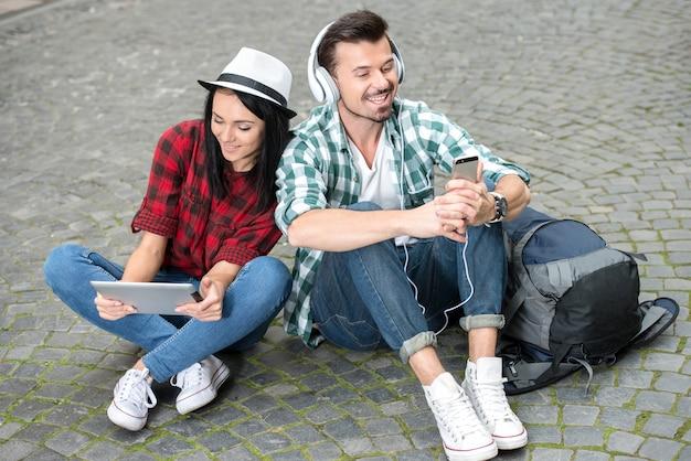Turistas novos dos pares com uma tabuleta e fones de ouvido na cidade.