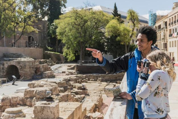 Turistas novos que tomam a foto do monumento romano