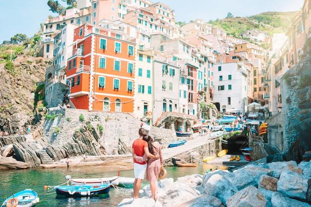 Turistas olhando a vista panorâmica de riomaggiore, cinque terre, ligúria, itália