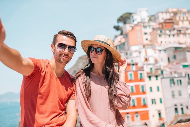 Turistas, olhando a vista panorâmica de riomaggiore, cinque terre, ligúria, itália