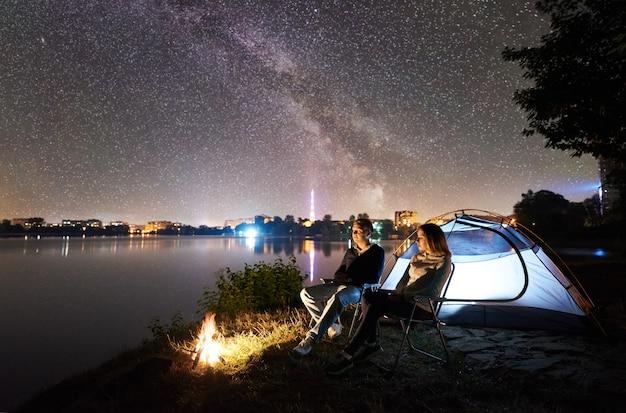 Turistas perto da barraca na margem do lago à noite