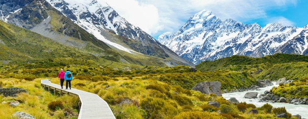 Turistas que caminham na trilha do vale do navio de pesca a linha no parque nacional do cozinheiro da montagem, nova zelândia.