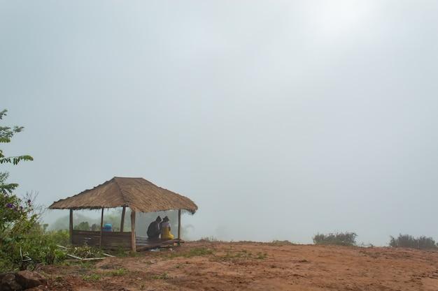 Turistas que prestam atenção à névoa na montanha nas cabanas.