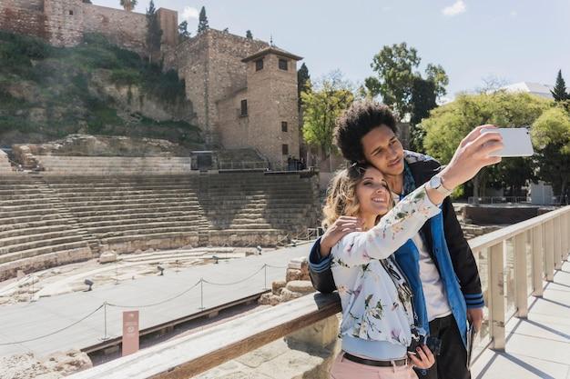Turistas que tomam selfie na frente do monumento romano