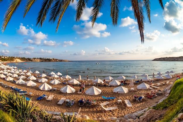 Turistas relaxando na praia durante as férias de verão. aldeia de peyia, distrito de paphos, chipre.