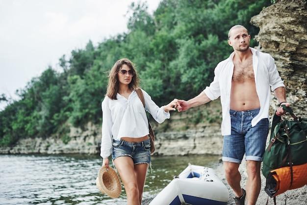 Turistas satisfeitos com a viagem que fazem no fundo de árvores perto do barco.