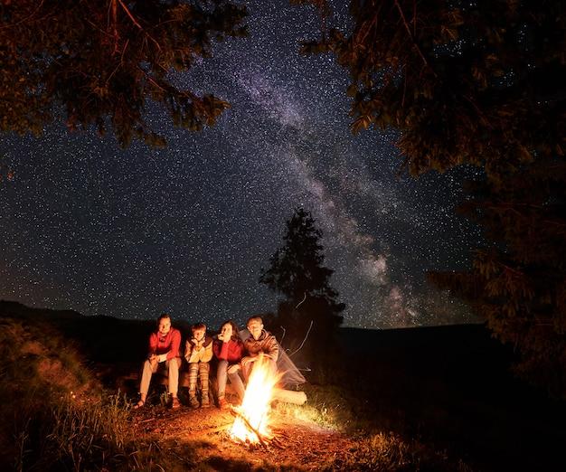 Turistas sentados em um tronco perto da fogueira com uma grande chama sob os pinheiros sob o céu extraordinário repleto de estrelas.