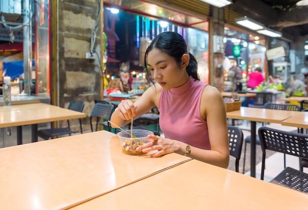 Turistas tailandeses-chineses passeiam e experimentam comida de rua em yaowarat road, chinatown, bangkok