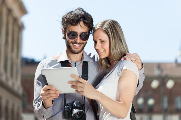 Turistas usando um tablet digital em uma cidade