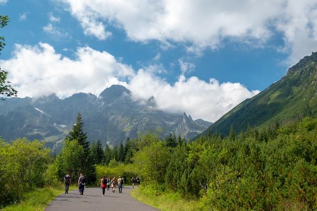 Turistas vão ao longo da trilha nas montanhas