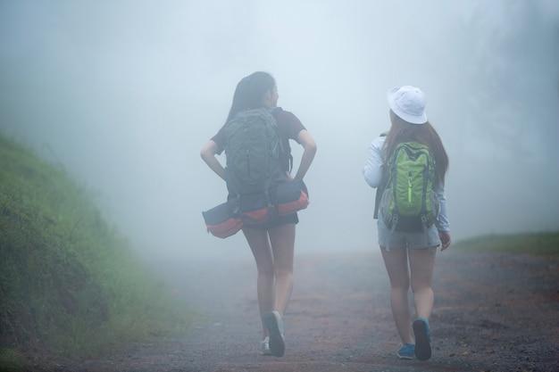 Turistas viajam caminhando na presença de neblina