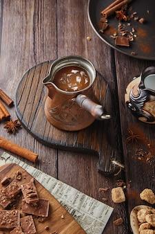 Turk com um cabo de madeira com cacau, chocolate com uma bebida quente em uma mesa de madeira, chocolate e canela, um café festivo. lugar para texto