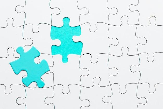 Turquesa pedaço de quebra-cabeça no cenário de quebra-cabeça branca