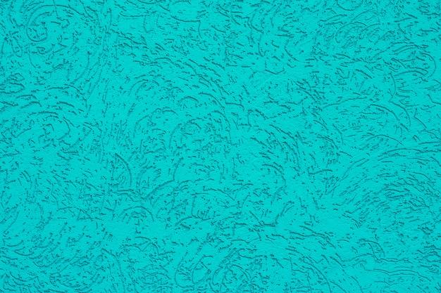 Turquesa pintou a textura com ornamento abstrato, fundo da cor do aqua, parede verde com nervuras decorativa.