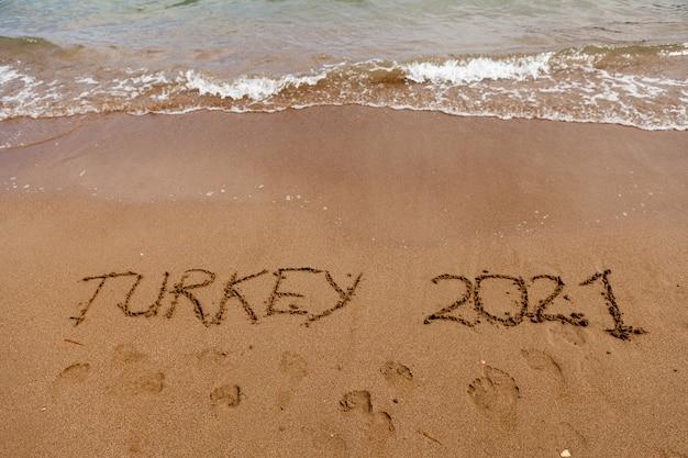 Turquia a inscrição na areia da praia turca ao lado das ondas das férias do mar em tu ...