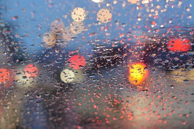Turva luz do carro na chuva para o fundo