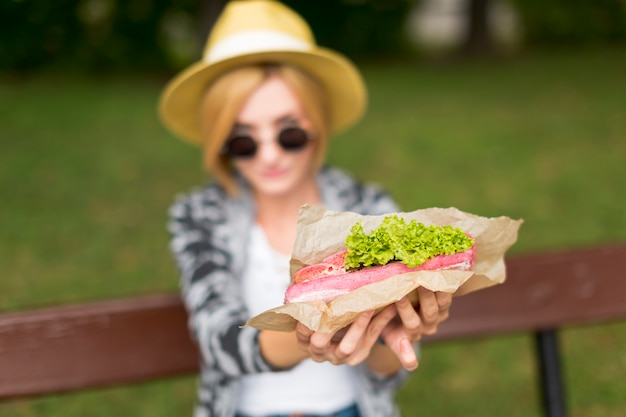 Turva mulher segurando um sanduíche fresco