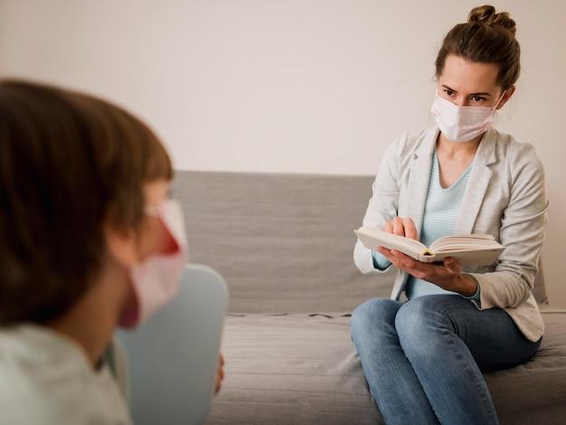 Tutor com máscara médica ensinando criança em casa