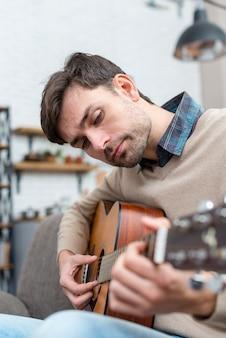 Tutor de vista lateral tocando violão