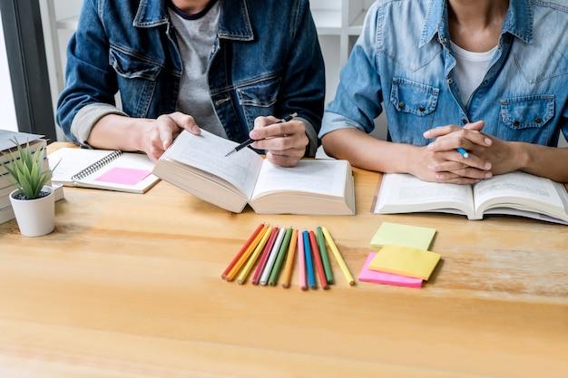 Tutor do ensino médio ou grupo de estudantes universitários sentado na mesa na biblioteca, estudando e lendo, fazendo lição de casa