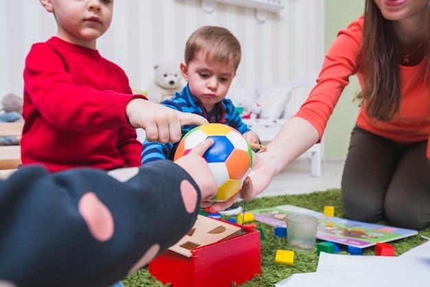 Tutor e crianças jogando bola