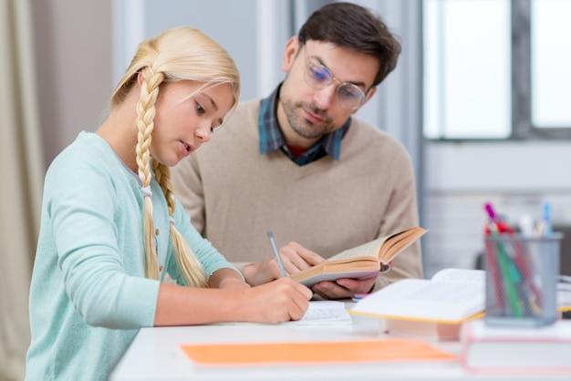 Tutor e menina em casa escrevendo