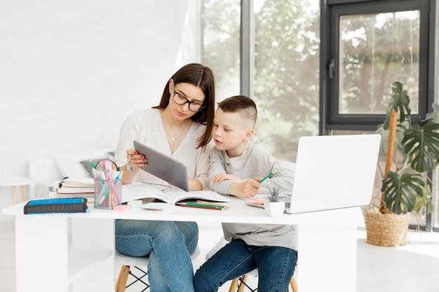 Tutor e menino aprendendo em casa