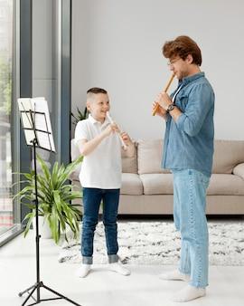 Tutor e menino aprendendo um instrumento musical