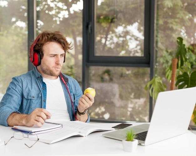 Tutor em casa comendo uma maçã e sentado em sua mesa
