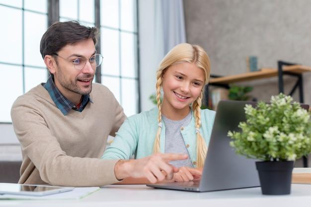 Tutor em casa e aluno olhando para a tela