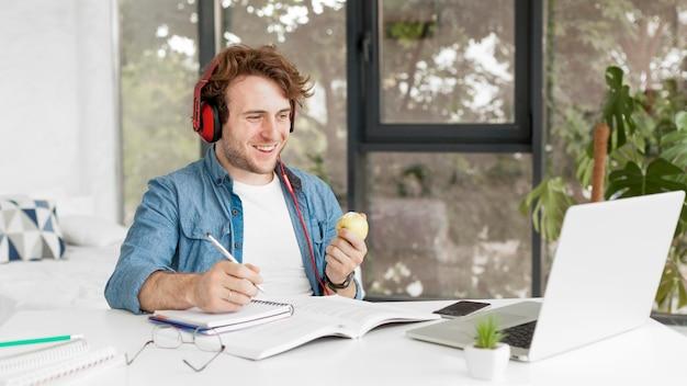 Tutor em casa segurando uma maçã e sorrisos