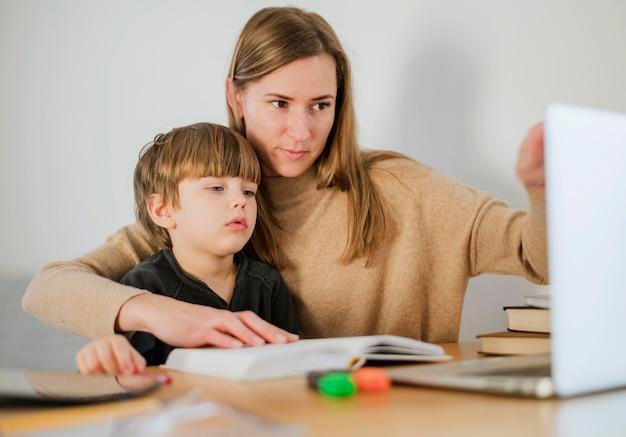Tutor fêmea que ensina a criança em casa usando o portátil
