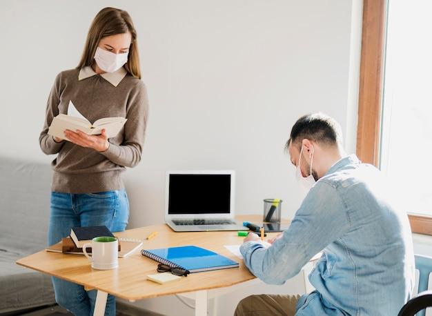 Tutor feminino com máscara médica, observando o estudante do sexo masculino