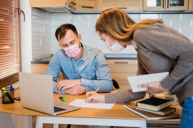 Tutor feminino corrigindo estudante do sexo masculino em casa