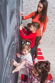 Tutor feminino desenhando na lousa com crianças