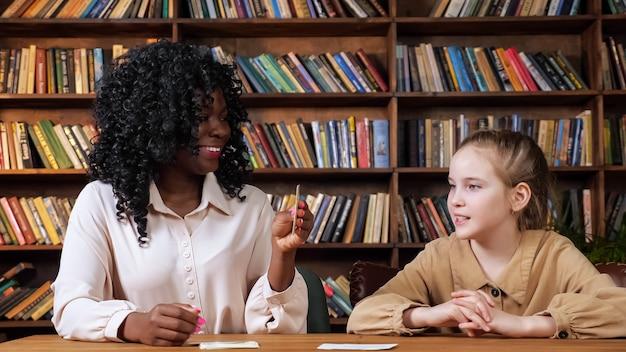 Tutor individual ensina cartas a meninas com flashcards