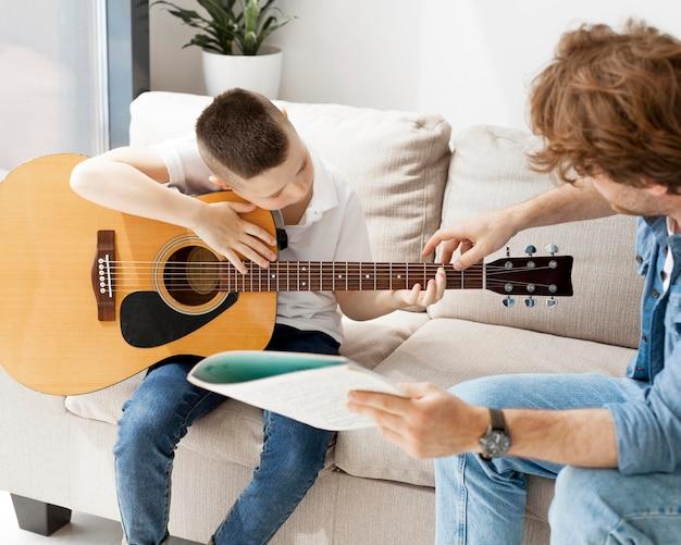 Tutor mostrando ao aluno como segurar a mão na guitarra