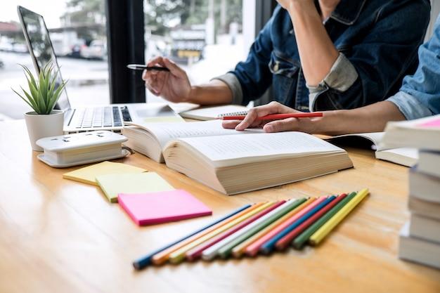 Tutor ou grupo de estudantes universitários sentado na mesa na biblioteca, estudando e lendo, fazendo lição de casa