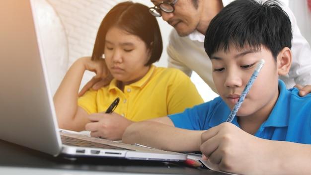 Tutor quarto crianças na aprendizagem de classe no computador portátil