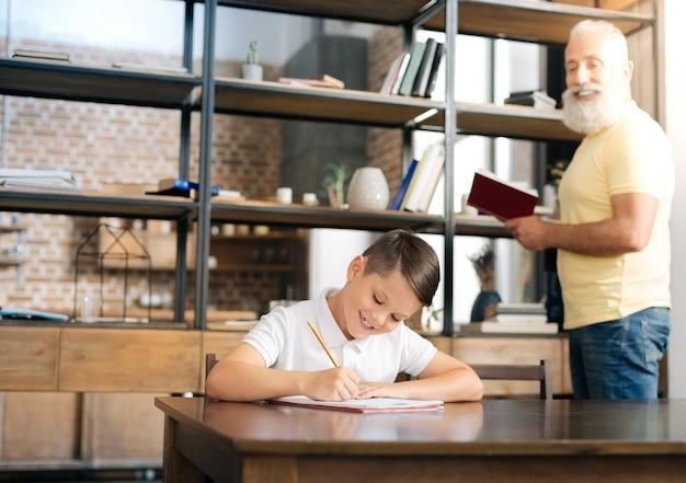 Tutor útil. homem sênior encantador segurando um livro e ditando uma passagem dele enquanto o neto o põe de lado e pratica a ortografia