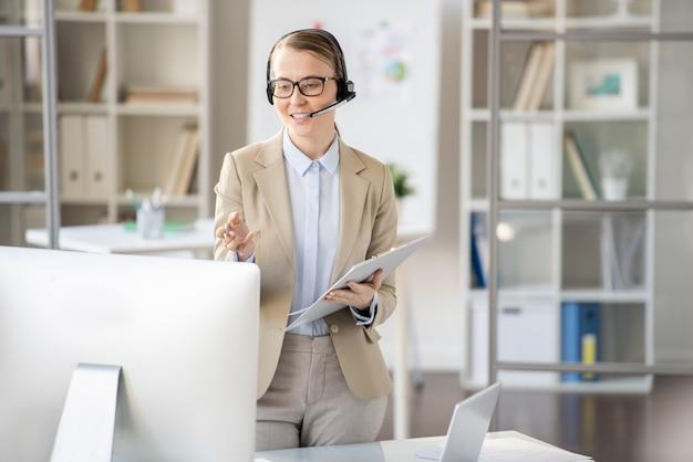 Tutora de webinar jovem confiante de conteúdo com fone de ouvido e óculos em pé na frente do computador e gesticulando com a mão enquanto segura a apresentação online, conceito de videoconferência