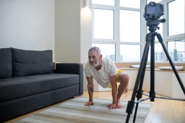 Tutorial online. um homem maduro de camiseta branca gravando um tutorial de ioga online