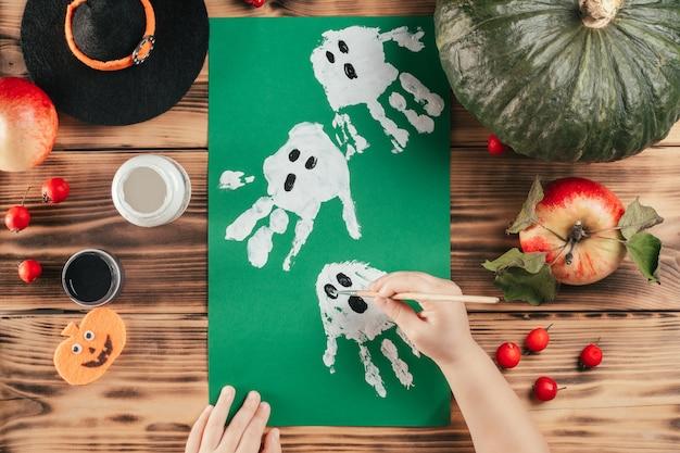 Tutorial passo a passo de halloween com impressão de mão de fantasmas. etapa 8: as mãos das crianças atraem os olhos e a boca dos fantasmas. vista do topo