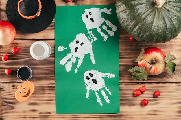 Tutorial passo a passo do dia das bruxas impressão da mão da criança fantasmas. etapa 9: desenho final de fantasmas feito com as impressões das mãos de crianças. vista do topo