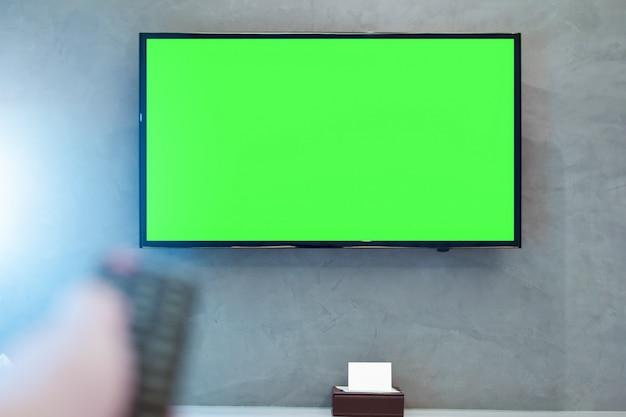 Tv de tela led com tela verde na parede no quarto moderno com remoto borrado