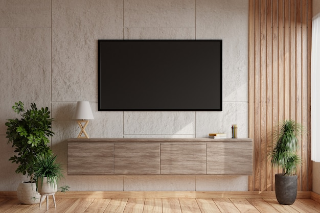 Tv em uma parede de concreto branco em uma sala de estar moderna com uma lâmpada e livros colocados em um armário de madeira e decorado com um vaso de plantas no chão de madeira.