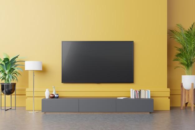 Tv no armário na moderna sala de estar com lâmpada, mesa, flor e planta no fundo da parede amarela.